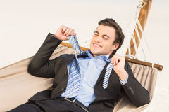 Businessman removing his tie on the hammock Royalty Free Stock Photo