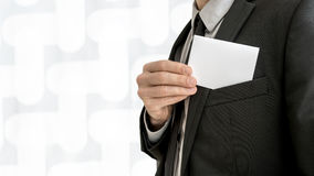 Businessman removing or placing a blank white business card in a Stock Image
