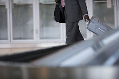 Businessman removing suitcase from luggage carousel in baggage claim Royalty Free Stock Images