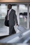 Businessman removing suitcase from luggage carousel in baggage claim stock photo