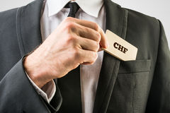 Businessman removing a wooden card with CHF sign Stock Photography