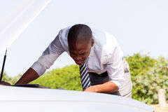 Businessman repairing broken car Royalty Free Stock Image