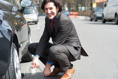 Businessman repairing car roadside Stock Photo