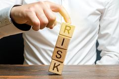 Businessman rescues with his finger a tower of cubes with the word Risk from falling Risk management, cost assessment, business. And investment safety stock photos