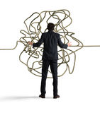 Businessman resolves the tangle. Businessman looks confused tangle of rope. Find a solution concept Stock Photo