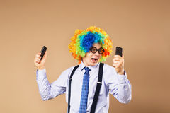 Businessman respond to numerous phone calls. Businessman holding. Two mobile phones. Close-up Portrait of business man in clown wig. Business concept stock photos