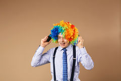 Businessman respond to numerous phone calls. Close-up Portrait of business man in clown wig. Business concept royalty free stock image