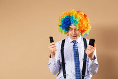 Businessman respond to numerous phone calls. Close-up Portrait of business man in clown wig. Business concept stock images