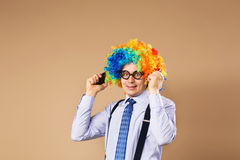 Businessman respond to numerous phone calls. Businessman holding two mobile phones. Close-up Portrait of business man in clown wig. Business concept royalty free stock image