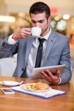 Businessman in the restaurant drinking coffee and working on dig Stock Image