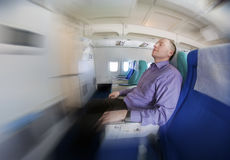 Businessman resting on a airplane Stock Photo