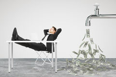 Businessman resting on a chair and faucet from which the money f Stock Photo