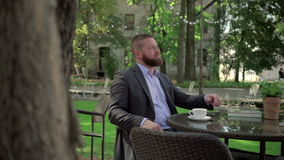 Businessman resting during coffe break. Outdoor. Steadicam shot. He is young and has beard. He is dressed on shirt and jacket. At backgroung there is garden stock video footage