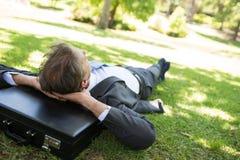 Businessman resting head on briefcase Stock Photos