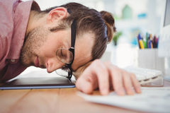 Businessman resting with head on desk Royalty Free Stock Image
