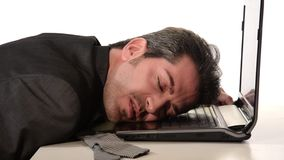Businessman resting head on laptop