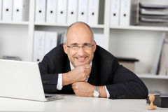 Businessman Resting His Chin On Fists At Office Desk Stock Photo