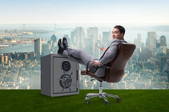 The businessman resting putting leg on safe Stock Photography