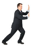 Businessman rests hands against wall stock photo