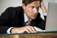 Businessman rests his head in one hand while worki Royalty Free Stock Photos