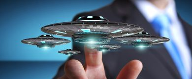 Businessman with retro UFO spaceship 3D rendering. Businessman on blurred background with retro UFO spaceship 3D rendering Royalty Free Stock Image