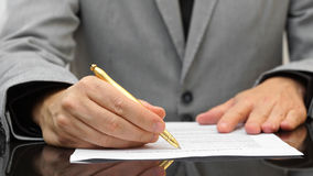 Businessman is reviewing agreement with gold pen royalty free stock photography