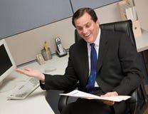 Businessman reviewing file folder at desk. Excited businessman reviewing file folder at desk in cubicle Stock Image