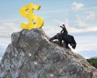Businessman riding bear pursuing gold dollar sign on mountain pe. Businessman riding black bear pursuing gold dollar sign on mountain peak with sky clouds royalty free stock photo