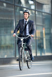 Businessman riding bicycle by building Royalty Free Stock Image