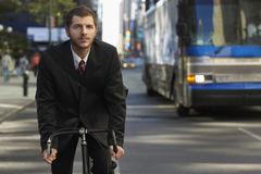 Businessman Riding Bicycle On City Street. Young businessman riding bicycle on city street stock images
