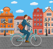 Businessman Riding a Bicycle. City style businessman with bag riding bicycle the streets of the old town. Bike to work poster. Including beautiful european Stock Photography