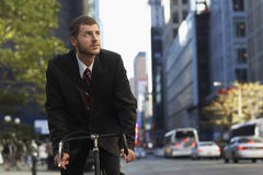 Businessman Riding Bicycle While Looking Away. Young businessman riding bicycle while looking away on urban street royalty free stock images