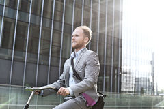 Businessman riding bicycle outside office building Royalty Free Stock Image