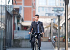 Businessman riding bicycle on street Royalty Free Stock Photo