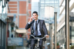 Businessman riding a bicycle and talking with mobile phone Stock Photography