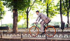 Businessman riding bicycle. To work in park Royalty Free Stock Photo