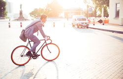 Businessman riding bicycle. To work in town Stock Image