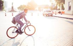 Businessman riding bicycle Stock Image