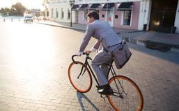 Businessman riding bicycle to work. On urban street in morning Royalty Free Stock Photography