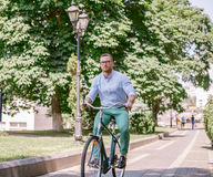 Businessman riding bicycle to work on urban street in morning. Lifestyle, transport, communication and people concept Royalty Free Stock Photography