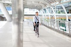 Businessman riding bicycle to work on urban street in morning .transport and healthy royalty free stock image