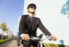 Businessman riding a bicycle to workplace for protecting environ Stock Photography