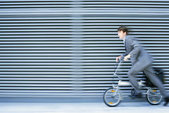 Businessman riding bicycle on urban sidewalk Royalty Free Stock Photo