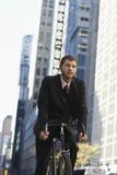 Businessman Riding Bicycle On Urban Street. Low angle view of young businessman riding bicycle on urban street royalty free stock images