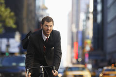 Businessman Riding Bicycle On Urban Street Royalty Free Stock Photos