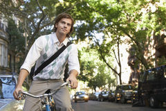 Businessman Riding Bicycle On Urban Street Stock Photo