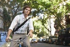 Businessman Riding Bicycle On Urban Street Stock Photo