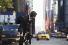 Businessman Riding Bicycle On Urban Street. Young businessman looking over shoulder while riding bicycle on urban street Stock Photography