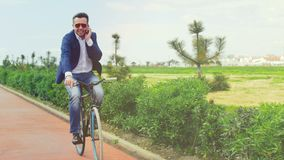 Businessman riding on bike on bicycle path in city park and talking by mobile. Phone. Man cycling on bike and calling to smartphone stock footage