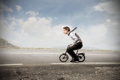 Businessman riding a bike Stock Photos